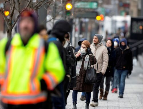 Canada coronavirus FILE PHOTO: A woman adjusts her mask while she waits in line as the city's public health unit holds a walk-in clinic testing for coronavirus disease (COVID-19) in Montreal
